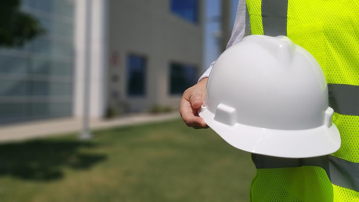 A person holding a hard hat - stock image